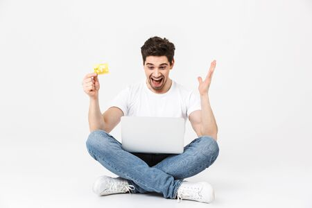 Full length portrait of a cheerful young man wearing casual clothing isolated over white background, sitting with laptop computer, showing credit card, celebrating Stockfoto
