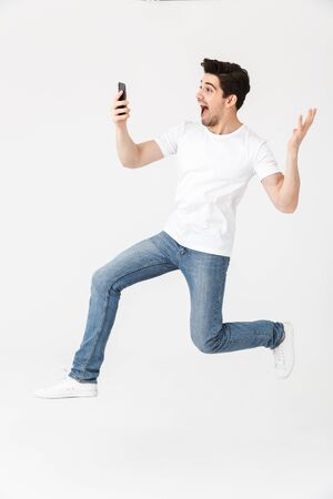 Image of excited happy young man posing isolated over white wall background using mobile phone jumping.