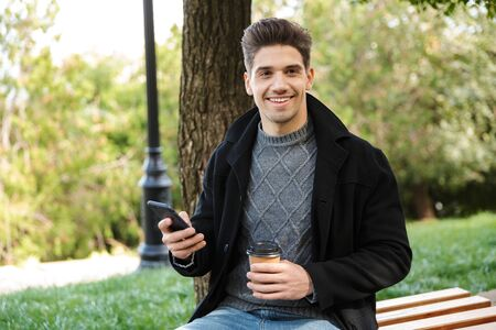 Photo of a handsome pleased young happy man in casual clothing walking outdoors in green park using mobile phone drinking coffee. Imagens