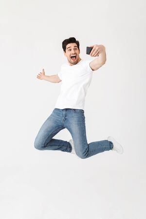 Image of excited happy young man posing isolated over white wall background using mobile phone take a selfie showing copyspace.