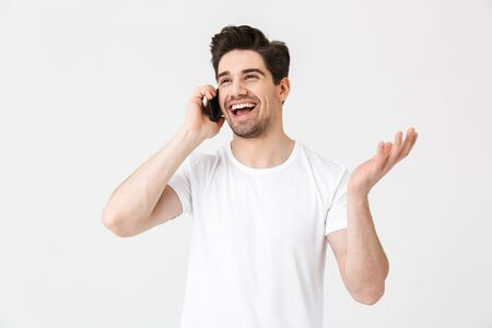 Image of happy young man posing isolated over white wall background talking by mobile phone.