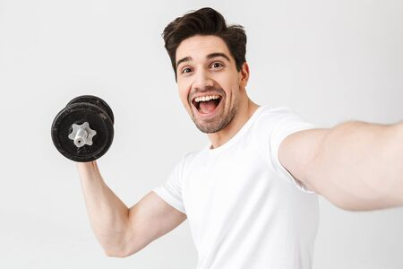 Image of emotional happy excited young man posing isolated over white wall holding dumbbell make exercise take a selfie by camera. Фото со стока - 128775864
