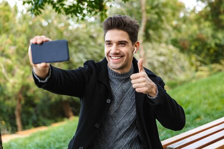 Image of optimistic young man in casual clothing walking outdoors in green park using mobile phone take a selfie with thumbs up gesture.