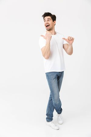 Full length portrait of a cheerful young man wearing casual clothing isolated over white background, presenting copy space Stock fotó