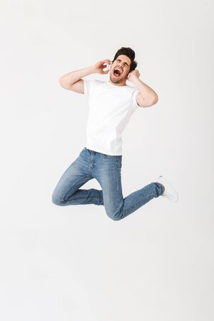 Image of emotional excited young man posing isolated over white wall background listening music with headphones jumping. 스톡 콘텐츠