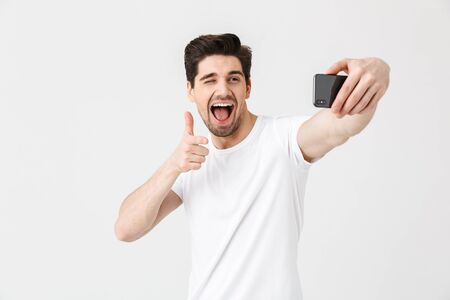 Image of happy emotional young man posing isolated over white wall background pointing take selfie by mobile phone.