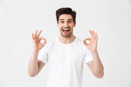 Ritratto di un giovane allegro che indossa abbigliamento casual isolato su sfondo bianco, ok