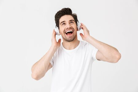 Image of emotional excited young man posing isolated over white wall background listening music with headphones. 스톡 콘텐츠