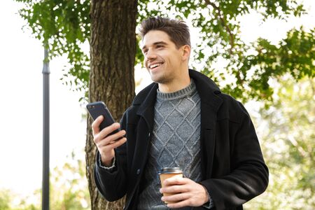 Image of a handsome smiling young man in casual clothing walking outdoors in green park using mobile phone drinking coffee.