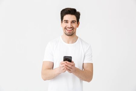 Image of excited happy young man posing isolated over white wall background using mobile phone.