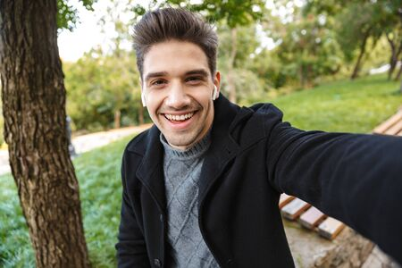 Image of smiling young man in casual clothing walking outdoors in green park take a selfie by camera.