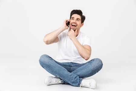 Image of a happy excited young man posing isolated over white wall background talking by mobile phone.