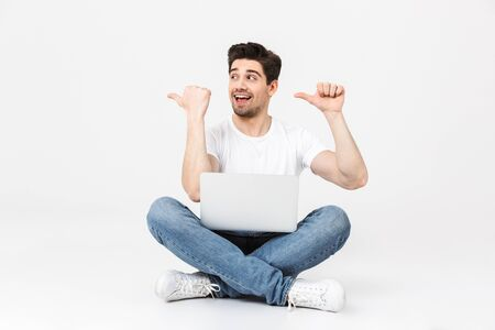 Full length portrait of a cheerful young man wearing casual clothing isolated over white background, sitting with laptop computer, pointing away
