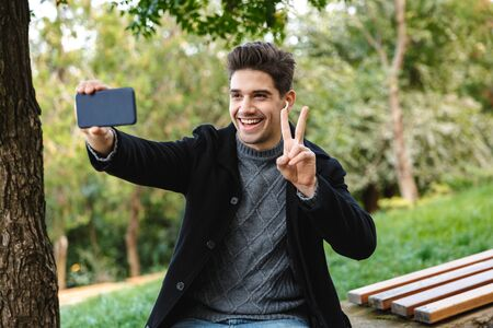 Picture of a smiling optimistic young man in casual clothing walking outdoors in green park using mobile phone take a selfie with peace gesture.