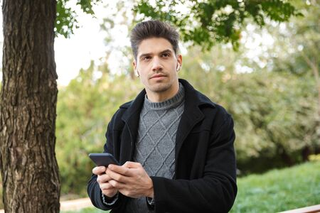 Photo of a serious handsome young man in casual clothing walking outdoors in green park using mobile phone listening music with earphones.