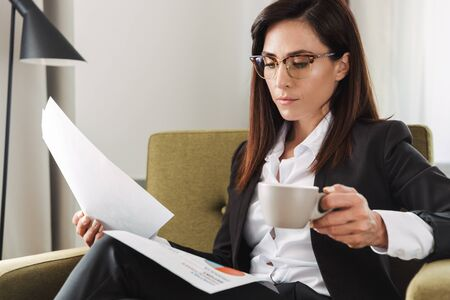 Image of a beautiful young business woman in formal wear clothes indoors at home drinking coffee work with documents.