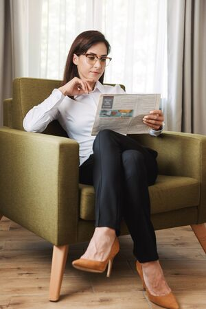 Image of an amazing concentrated beautiful young business woman in formal wear clothes indoors at home reading newspaper.