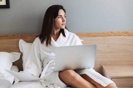 Portrait of thoughtful adult businesswoman in white bathrobe working with paper documents and laptop while lying on bed in apartment