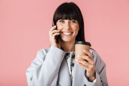 Image of a beautiful happy woman posing isolated over light pink background wall talking by mobile phone holding coffee.