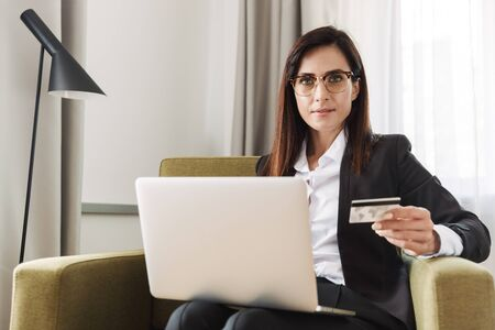 Photo of a beautiful young business woman in formal wear clothes indoors at home work with laptop computer holding credit card.
