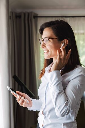 Image of an amazing happy beautiful young business woman in formal wear clothes indoors at home talking by mobile phone listening music with earphones using phone.