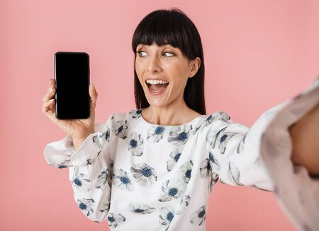 Image of a beautiful happy young woman posing isolated over pink wall background take selfie by camera showing display of mobile phone.