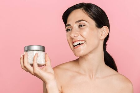 Beauty portrait of an attractive happy young topless woman standing isolated over pink background, holding sea salt