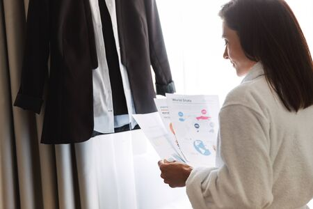Portrait of charming adult businesswoman in white bathrobe holding paper documents while standing near her formal suit in apartment