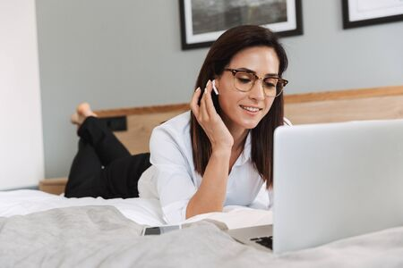 Portrait of elegant adult businesswoman in formal suit using laptop and earpods while lying on bed in apartment Stok Fotoğraf