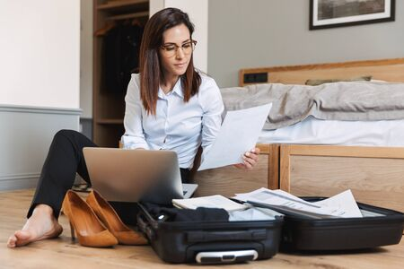 Portrait of confident adult businesswoman in formal suit working with paper documents and laptop while sitting on floor near luggage in apartment