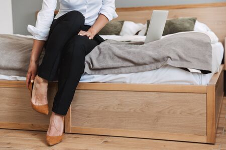 Cropped portrait of caucasian adult businesswoman in formal suit taking off her shoes while sitting on bed and using laptop in apartment