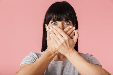 Image of a beautiful amazing scared shocked woman posing isolated over light pink background wall covering mouth. Stock Photo
