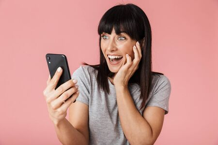 Image of a beautiful amazing excited happy woman posing isolated over light pink background wall using mobile phone.