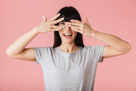 Image of a beautiful amazing happy woman posing isolated over light pink background wall covering eyes. Stock Photo
