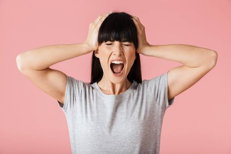 Image of a beautiful amazing shocked woman posing isolated over light pink background wall screaming.