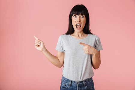 Image of a beautiful amazing woman posing isolated over light pink background wall pointing. Stock Photo