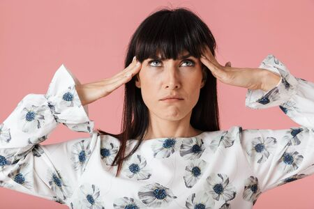Image of a beautiful amazing thinking serious woman with headache posing isolated over light pink background wall.