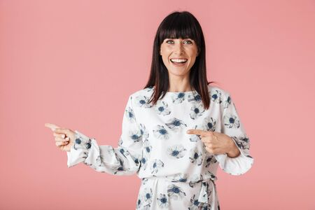 Image of a beautiful excited young woman posing isolated over pink wall background pointing. Stock Photo