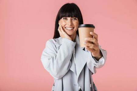 Image of a beautiful happy woman posing isolated over light pink background wall holding coffee. Stock Photo