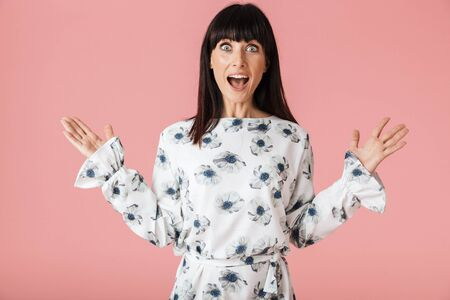 Image of a beautiful amazing shocked woman posing isolated over light pink background wall.