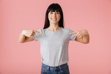 Image of a beautiful amazing woman posing isolated over light pink background wall pointing to herself.