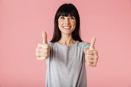 Image of a beautiful amazing happy woman posing isolated over light pink background wall showing thumbs up gesture.