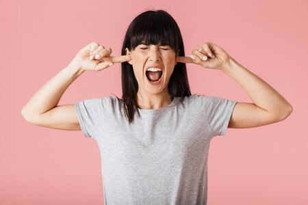 Image of a beautiful displeased woman posing isolated over light pink background wall covering ears.