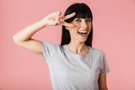 Image of a beautiful amazing woman posing isolated over light pink background wall showing peace gesture.