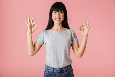 Image of a beautiful amazing woman posing isolated over light pink background wall showing okay gesture. Stock Photo