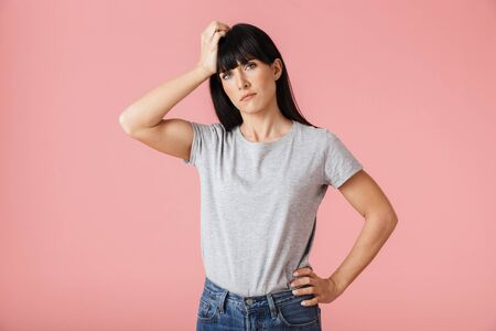 Image of a beautiful sad displeased woman with headache posing isolated over light pink background wall.