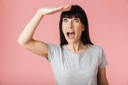 Image of a beautiful amazing happy excited woman posing isolated over light pink background wall looking aside.