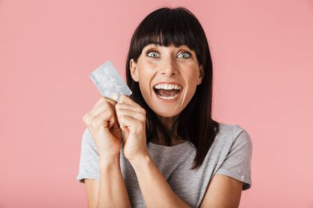Image of a beautiful amazing excited happy woman posing isolated over light pink background wall holding credit card.