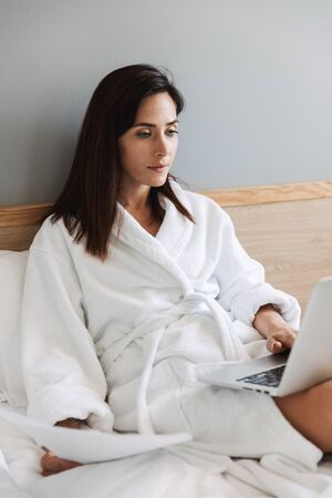 Portrait of charming adult businesswoman in white bathrobe working with paper documents and laptop while lying on bed in apartment