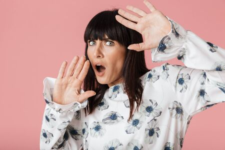 Image of a beautiful amazing scared shocked woman posing isolated over light pink background wall.